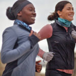 Two women smiling while running
